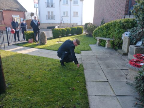 Royal British Legion member laying a cross for remembrance.